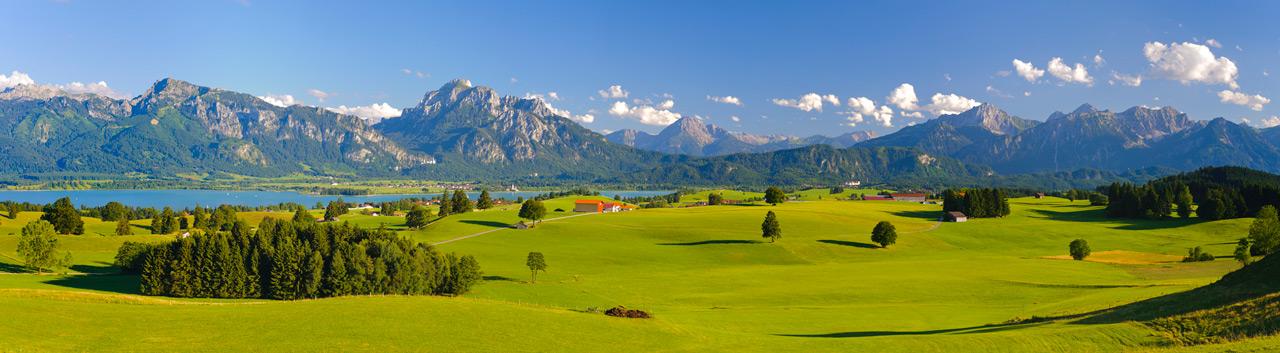 Panorama Landschaft in Bayern am Forggensee mit Blick auf die Alpenkette mit Berg Säuling, dem Hausberg der Stadt Füssen